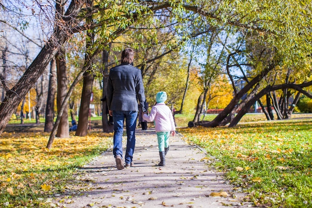 Rear view of young father and little girl walking in autumn park Premium Photo