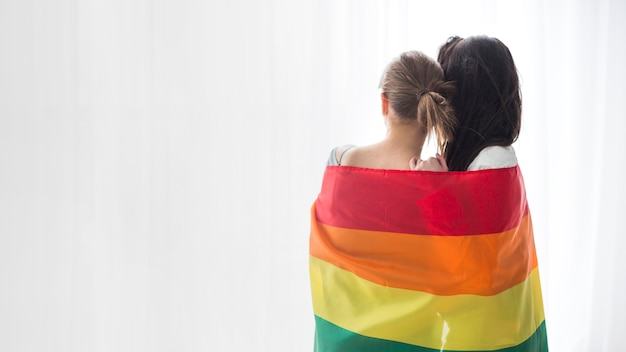 Rear view of young lesbian couple wrapped in rainbow flag looking at curtain Premium Photo