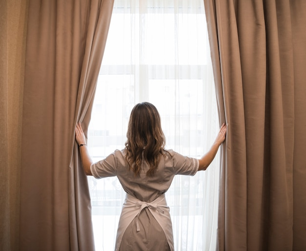 Rear view of a young maid opening curtains in hotel room Free Photo