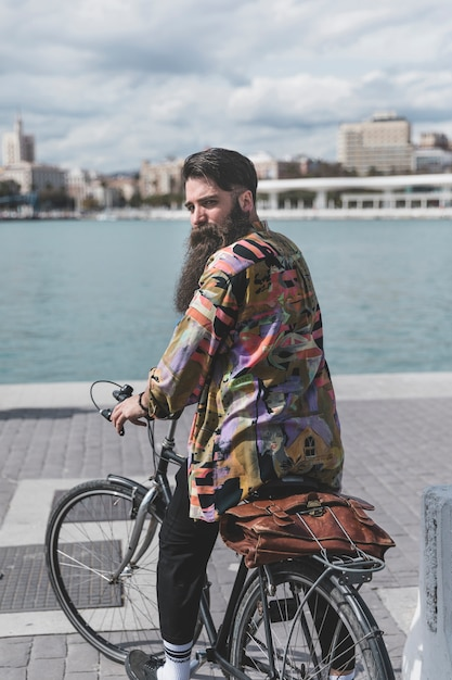 Rear view of a young man sitting on bicycle looking over shoulder near the coast Free Photo