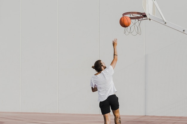Rear view of a young man throwing basketball in hoop Free Photo