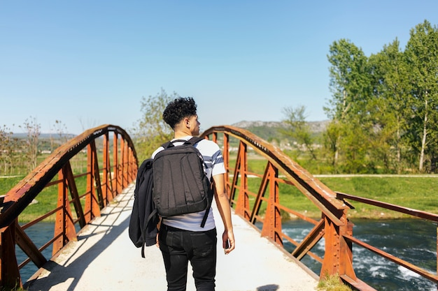 Rear view of young man walking on bridge over beautiful river Free Photo