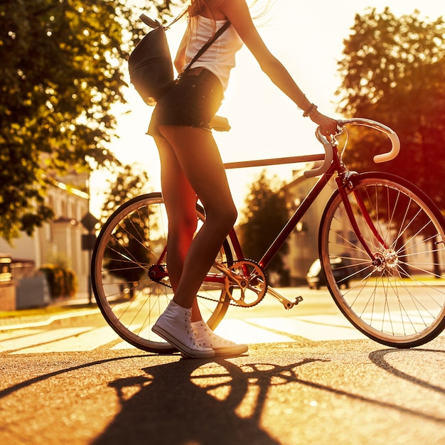 Rear view of young woman holding her bicycle at sunset Free Photo
