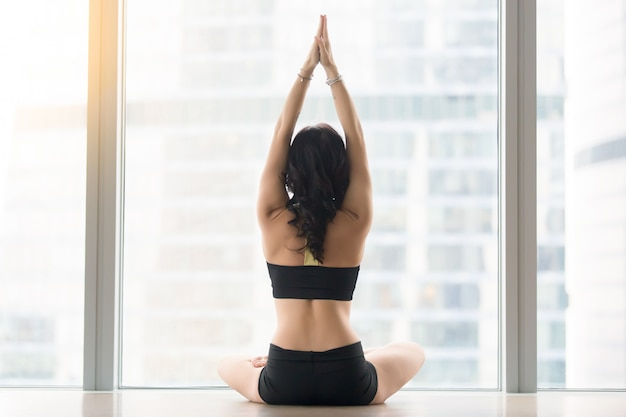 Rear view of young woman sitting in ardha padmasana pose Free Photo