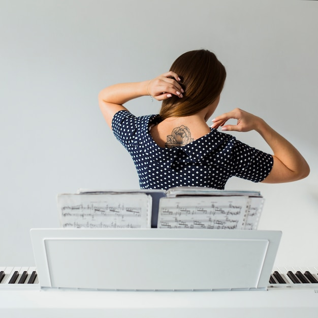 Rear view of young woman standing behind the piano showing tattoo over her back Free Photo