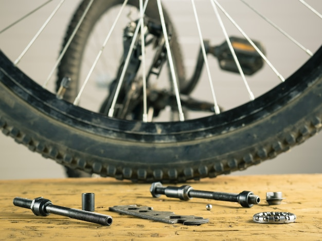 Rear wheel mountain bike and tools on a wooden table. Premium Photo