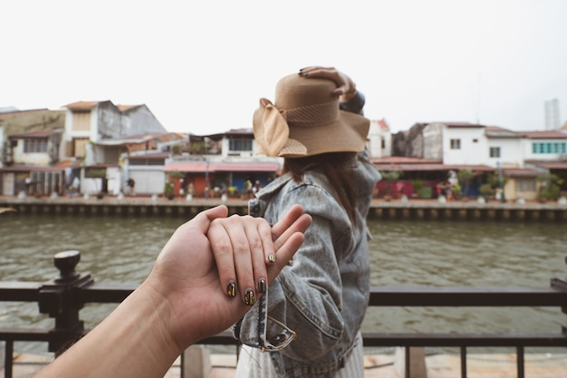 Rear of woman holding man hand leading for travel in malacca, malaysia Premium Photo