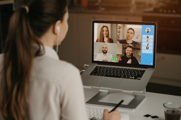 A rearview of a businesswoman at home in a video conference with her colleagues during an online meeting. partners in a video call. multiethnic business team having a discussion in an online meeting. Premium Photo