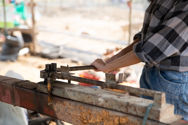 Rebar bending by worker on rusty jig in construction site Free Photo