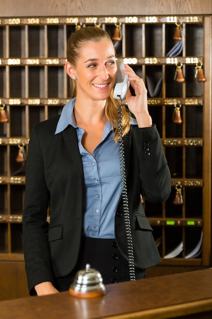 Reception of hotel, desk clerk taking a call Premium Photo