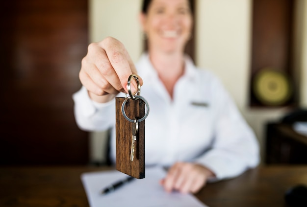 Receptionist handing room key to guest Premium Photo