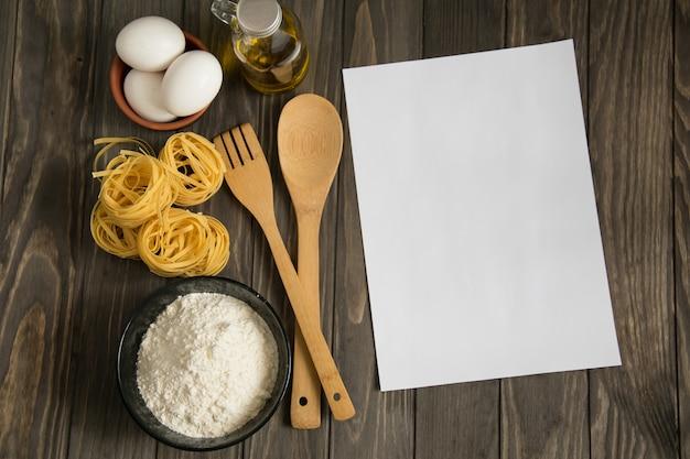 小麦粉、パスタ、卵、瓶の中の油、木のスプーンとフォークで木製の表面ボウルのレシピモックアップ Premium写真