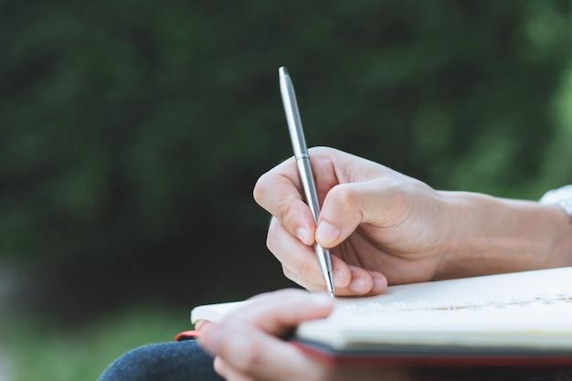 クローズアップ手若い男が公園で本にrecord lectureメモ帳を書くペンを使用して座っています。 Premium写真