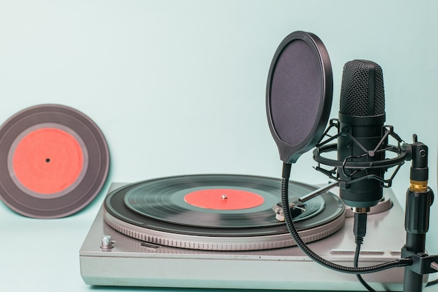 A record player with red vinyl discs and a modern microphone. Premium Photo