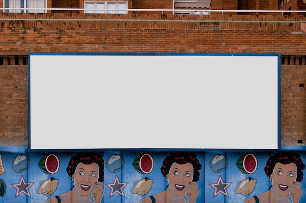 Rectangular billboard on brick wall with graffiti Free Photo