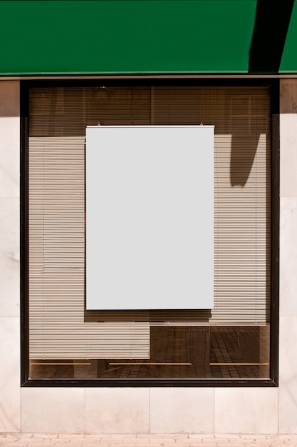 Rectangular blank billboard on glass window with blinds Free Photo