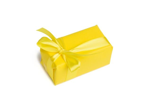 노란색 종이에 싸서 실크 노란색 리본, Wite 배경으로 묶인 선물이있는 직사각형 상자 프리미엄 사진