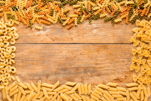 Rectangular frame made with different types of raw pasta on wooden table Free Photo