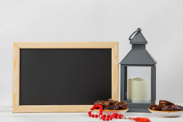 Rectangular small chalkboard with juicy dates and candle holder against white backdrop Free Photo