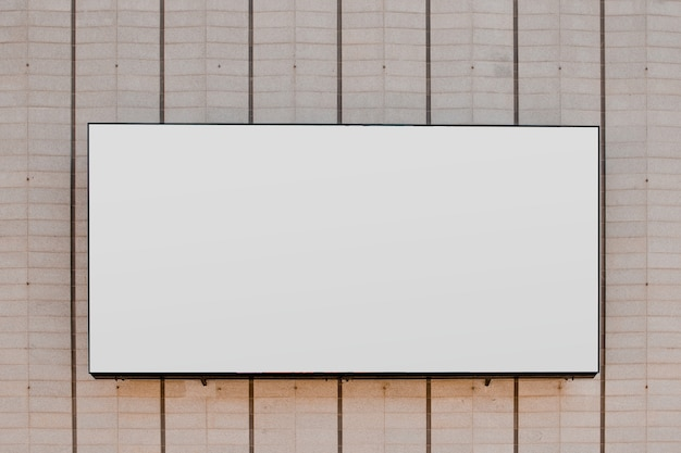 Rectangular white blank billboard on striped wall Free Photo