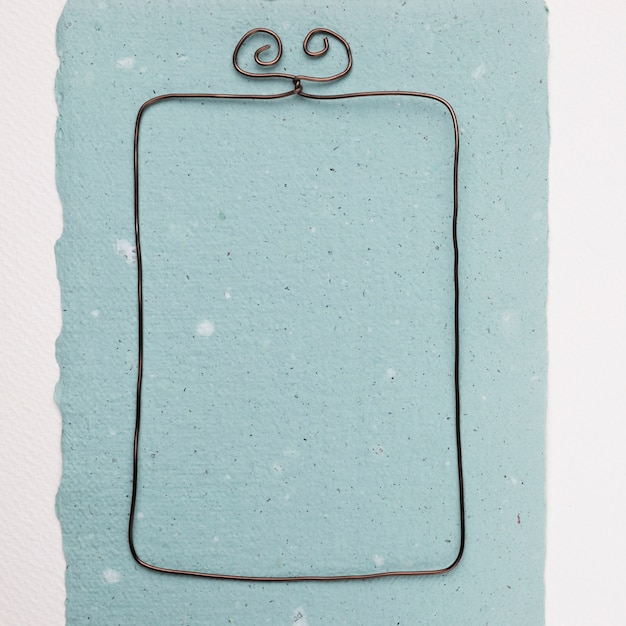 Rectangular wire frame on blue paper against white backdrop Free Photo