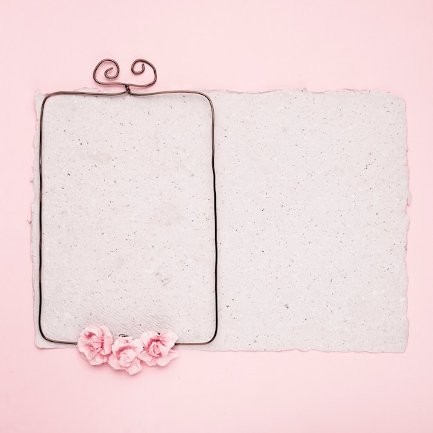 Rectangular wire frame decorated with roses on paper against pink background Free Photo