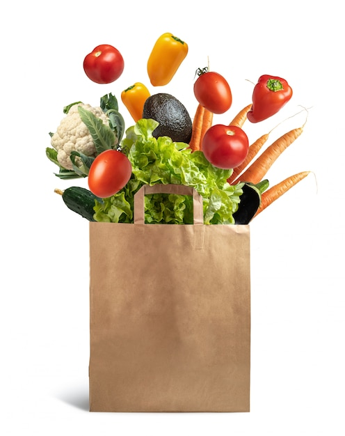 Recyclable paper bag with explosion of flying vegetables, concept healthy food and ecological recycling Premium Photo