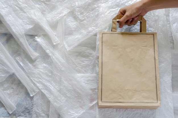 Recycle eco paper bag on top of white plastic. reuse and recycle for world environment concept. Premium Photo
