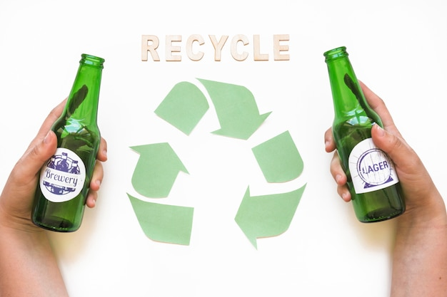Recycle lettering with symbol and hands with bottles Free Photo