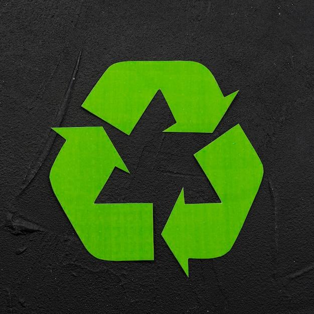 Recycle logo on black plaster background Free Photo