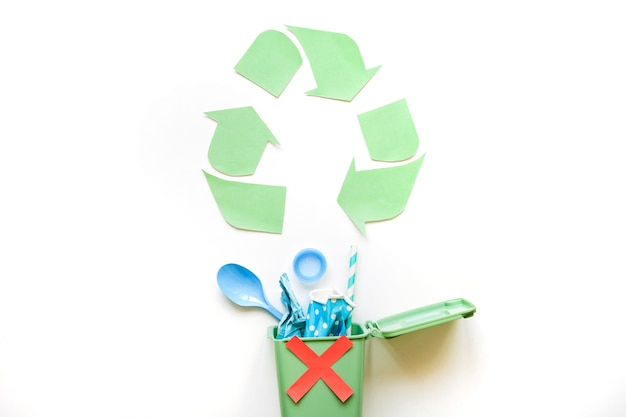 Recycle symbol and bin with plastic rubbish Free Photo