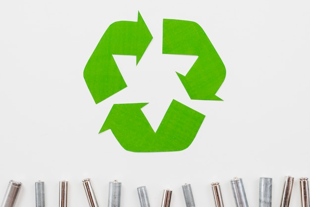 Recycle symbol and garbage batteries on grey background Free Photo