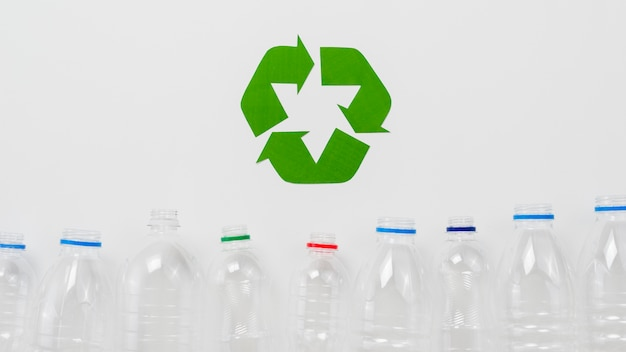 Recycle symbol and  plastic bottles on grey backgound Free Photo