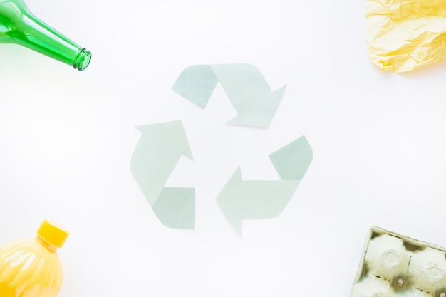 Recycle symbol with trash on corners Free Photo