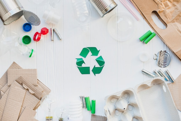 Recycle symbol with waste items on wooden white table Premium Photo