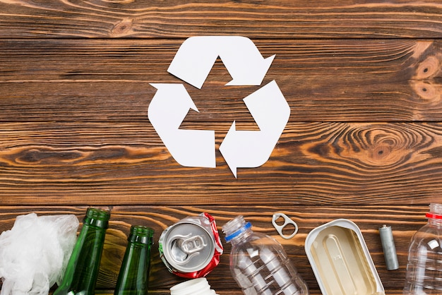 Recycling icon and trash on wooden background Free Photo