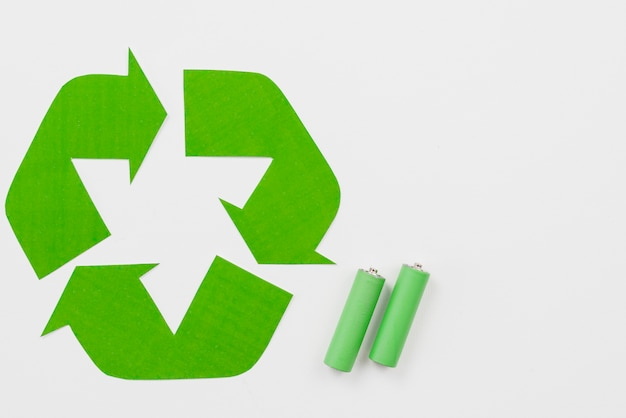 Recycling symbol beside green batteries Free Photo