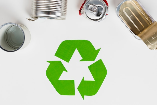 Recycling symbol beside used metallic packaging Free Photo