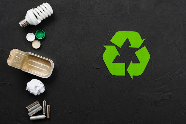 Recycling symbol beside various refuse Free Photo