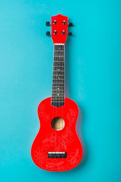 Красная акустическая классическая гитара на синем фоне Premium Фотографии