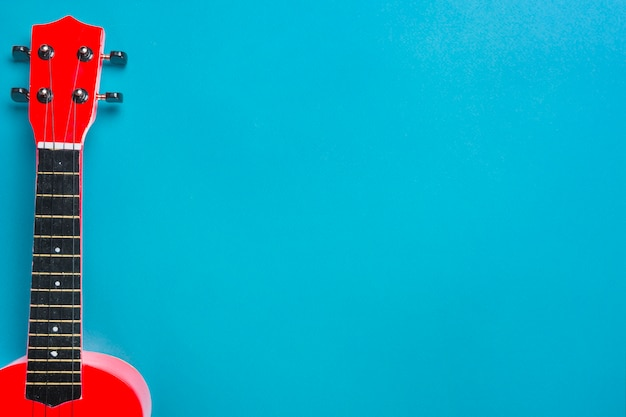 Red acoustic guitar on blue backdrop Premium Photo
