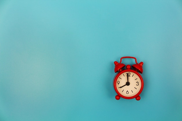 Red alarm clock on blue background. top view. flat lay. Premium Photo