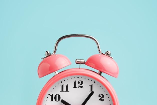 Red alarm clock on blue Premium Photo