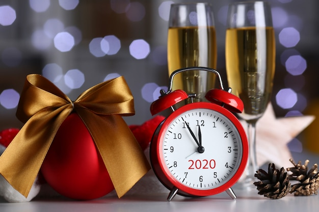 Red alarm clock and champagne goblet at office table Premium Photo