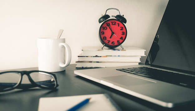 Red alarm clock on office table with objects Premium Photo