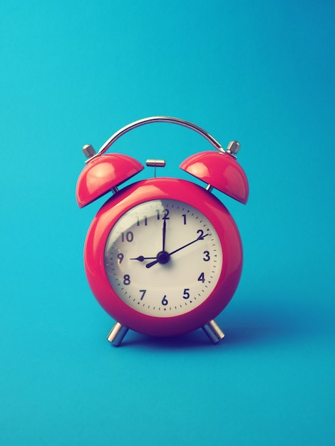 Red alarm clock on blue background Free Photo
