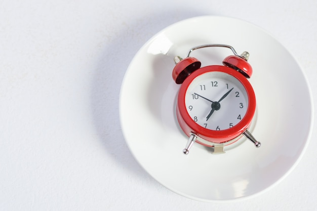 Red alarm clock on white plate with a silver spoon Premium Photo