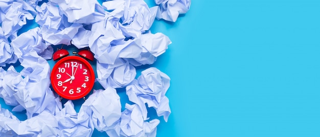 Red alarm clock with white crumpled paper balls on a blue background. Premium Photo