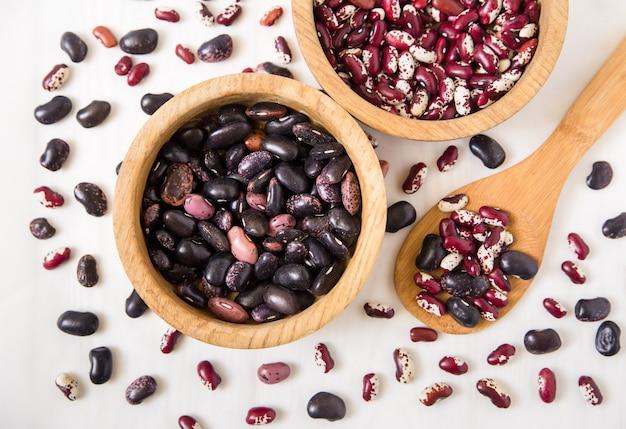 赤と黒のインゲン豆。木製の皿とスプーン。 Premium写真