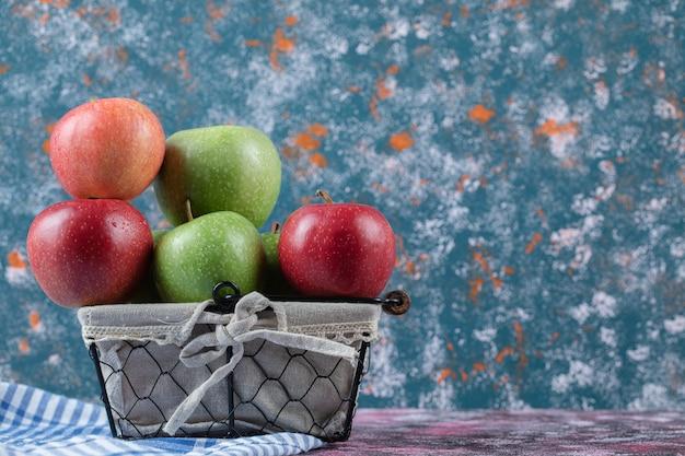 金属製のバスケットに入った赤と緑のリンゴ 無料写真